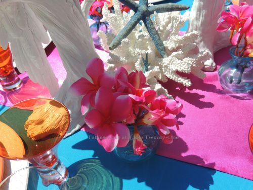 Fuchsia plumeria blossoms in Caribbean blue glass vase