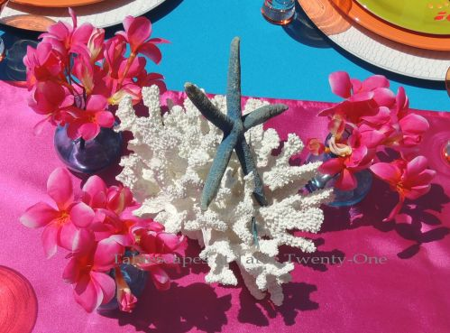Tablescapes at Table Twenty-One:Budget-friendly tropical centerpiece using white coral, dyed blue starfish with bright pink plumeria
