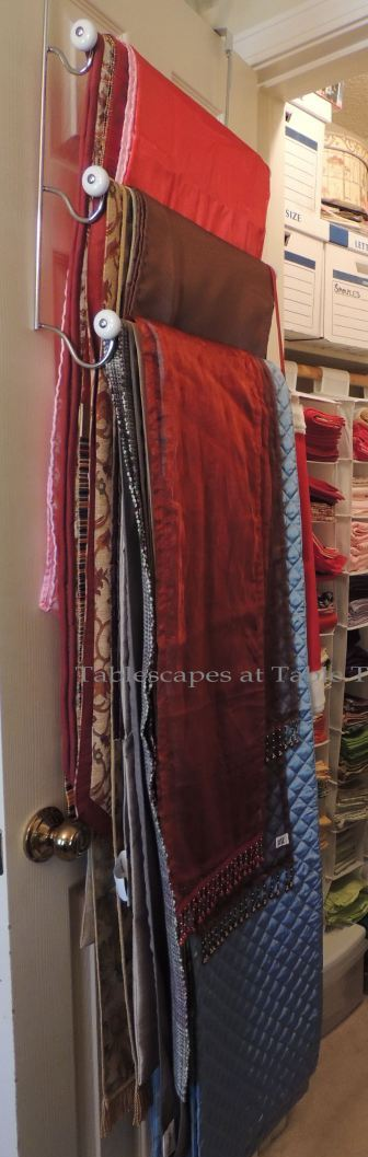 Hanging on a towel rack on the door are numerous table runner. The more casual runners are stored in the basement.