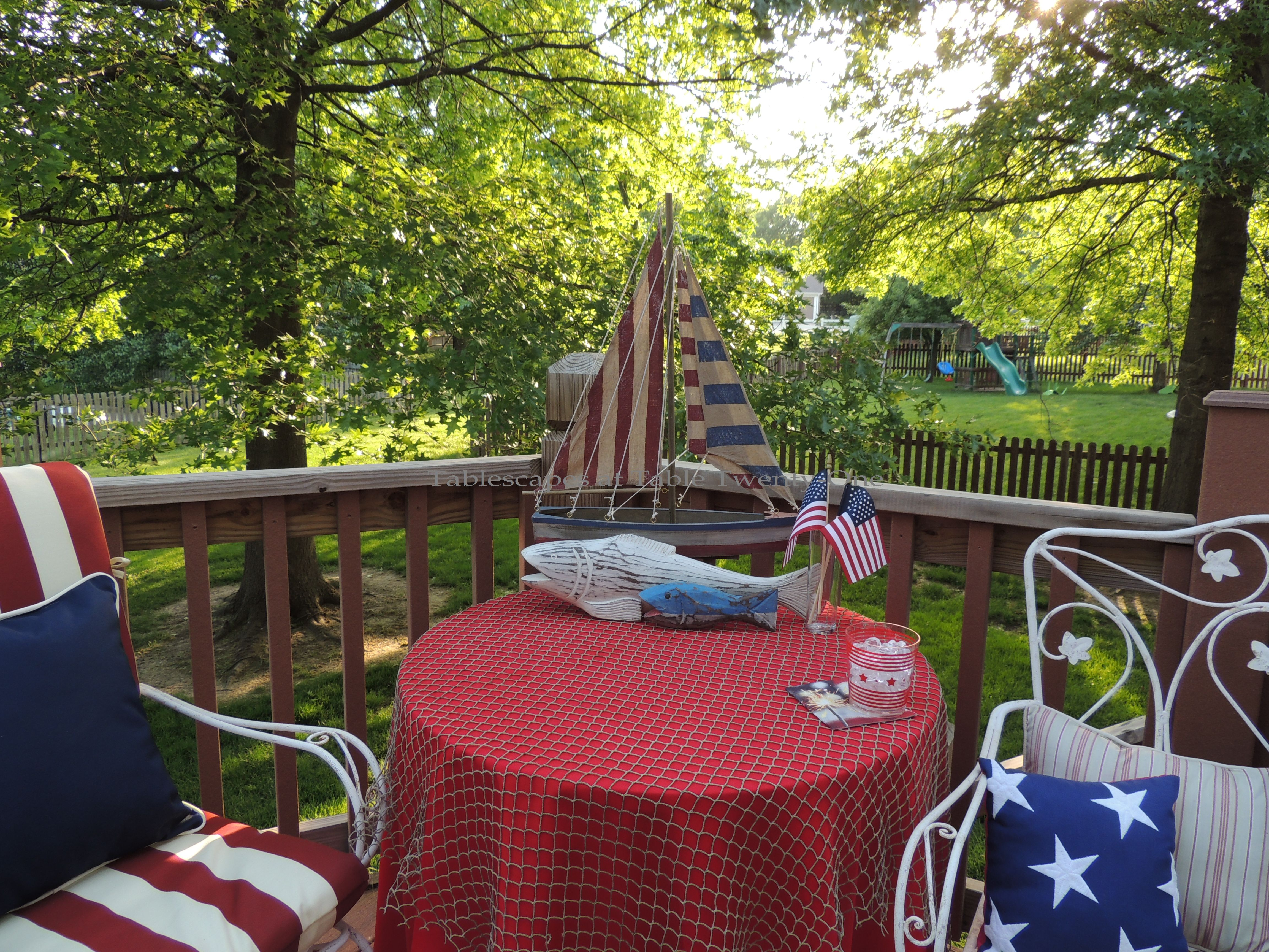 Tablescapes at Table Twenty-One, www.tabletwentyone.wordpress.com, 4th of July Coastal Style: Occasional table set up on deck with patriotic sailboat