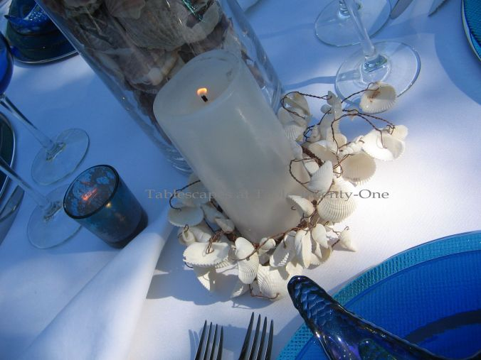 Tablescapes at Table Twenty-One, www.tabletwentyone.wordpress.com, Ocean Blue – Starfish & Seashells:  white pillar candle with Z Gallerie seashell candle ring
