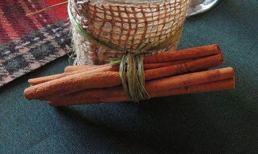 "Alycia Nichols, Tablescapes at Table Twenty-One, www.tabletwentyone.wordpress.com, ""Christmas in the Woods"": Cinnamon sticks tied with raffia on a burlap-wrapped votive holder"