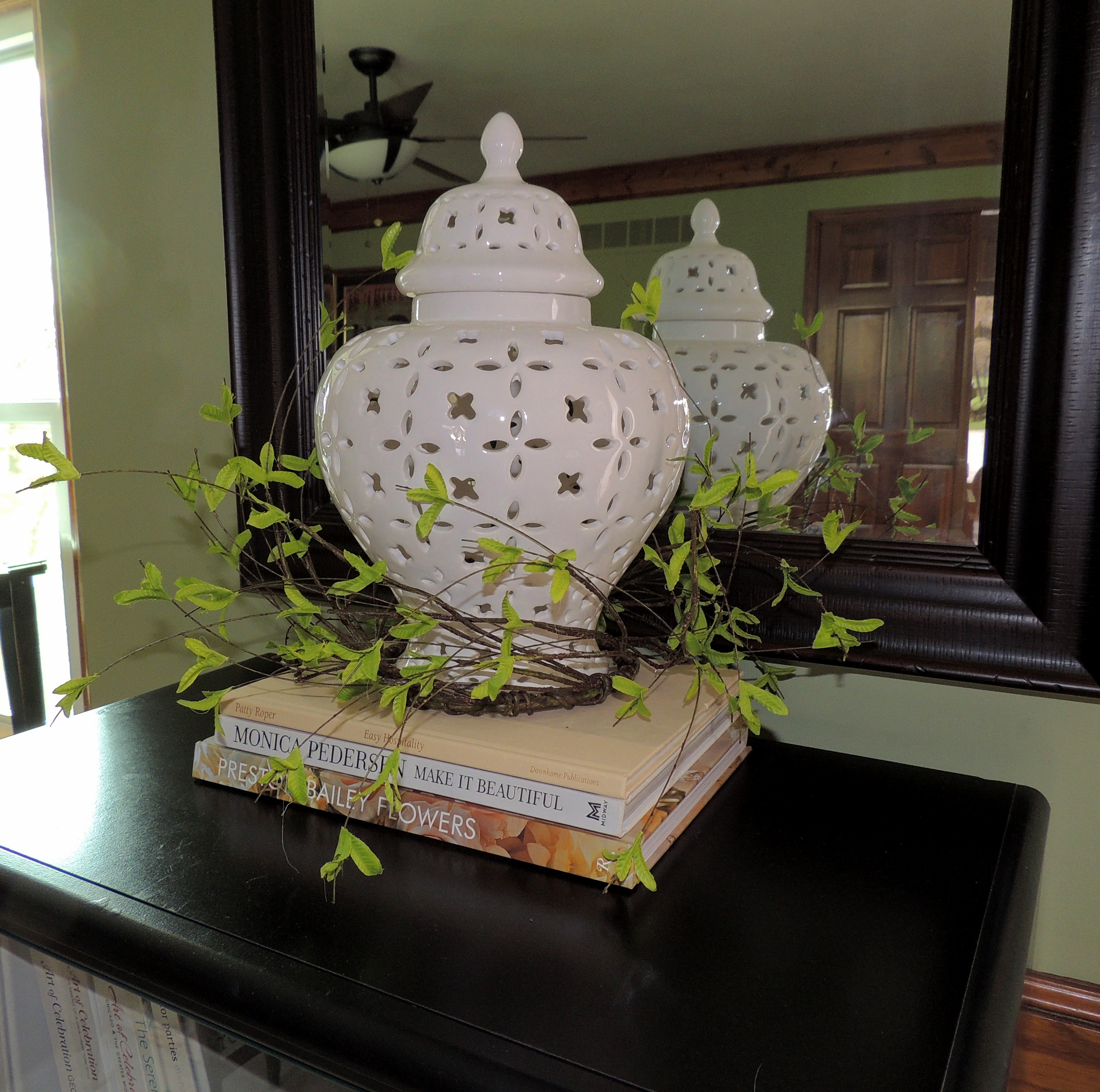 White pierced ginger jar on stack of books with airy wreath at the base. www.tabletwentyone.wordpress.com