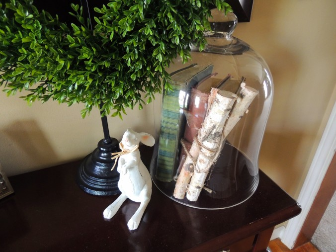 Weathered books and birch logs under glass cloche; wooden Easter bunny